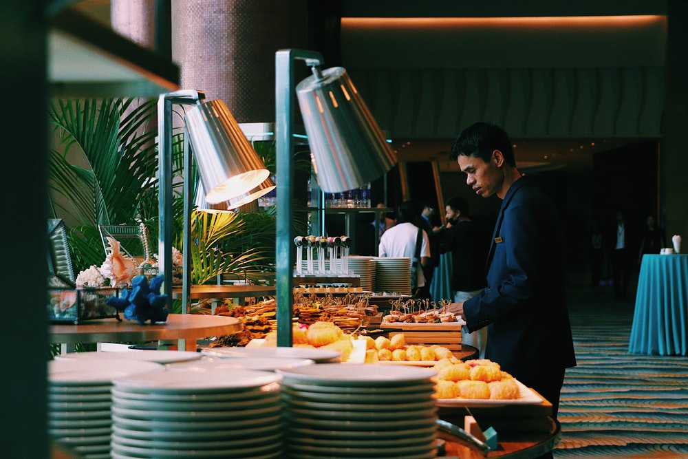 man pick some food at buffet table
