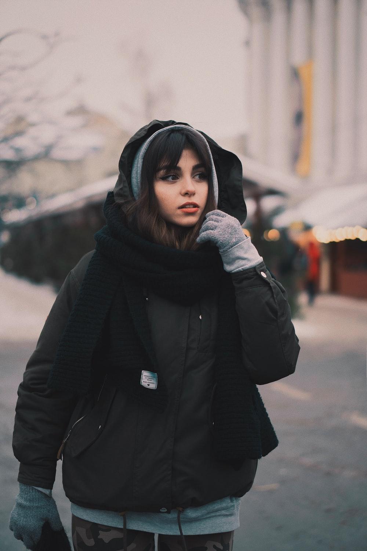 woman wearing black zip-up hooded jacket and black scarf