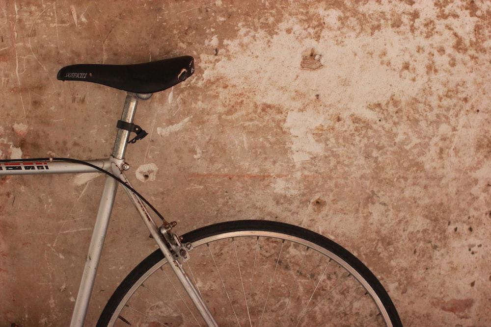 gray bike park near beige wall
