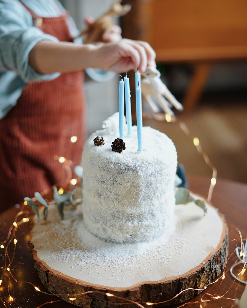 white unicorn cake topper above white cake with four blue candles