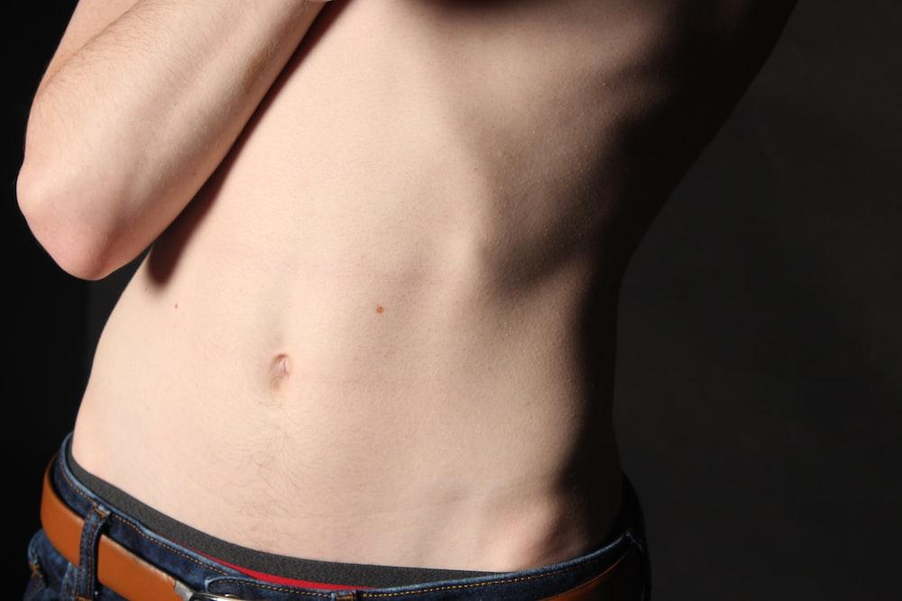 person wearing blue denim bottom's navel