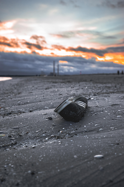 black and white Adidas shoe on shore