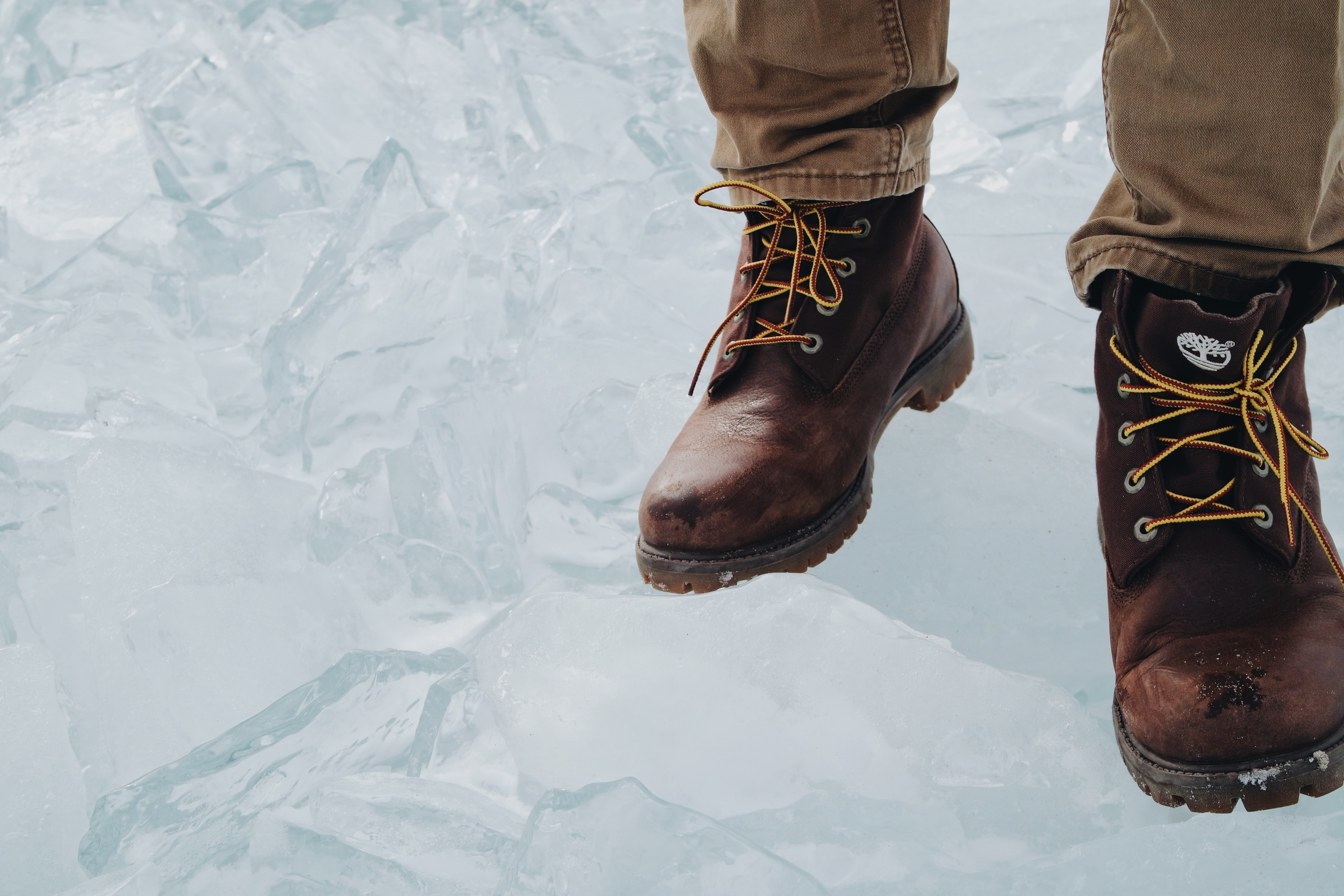person wearing brown boots walking on snow ground
