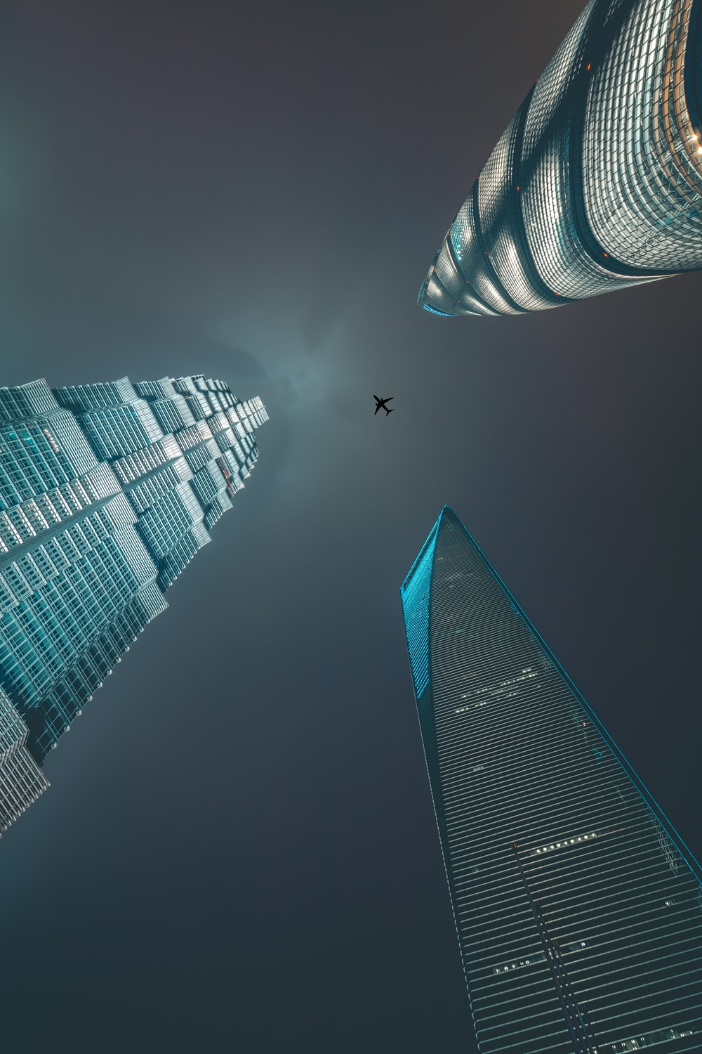 airliner flying over three high-rise buildings