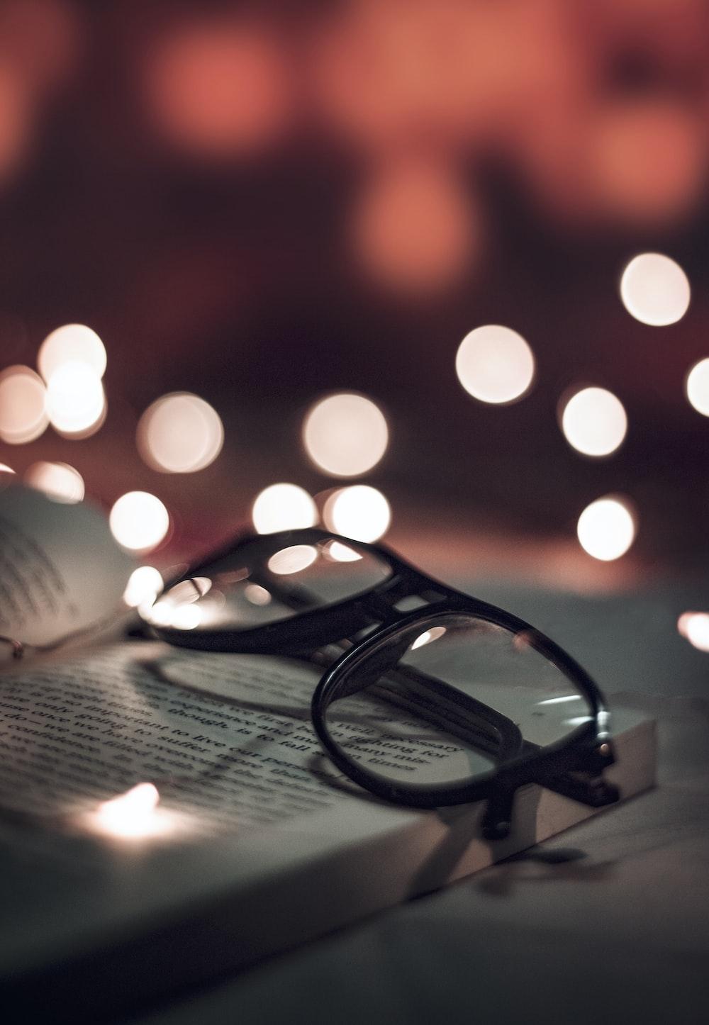 selective photo of black-framed eyeglasses on opened book
