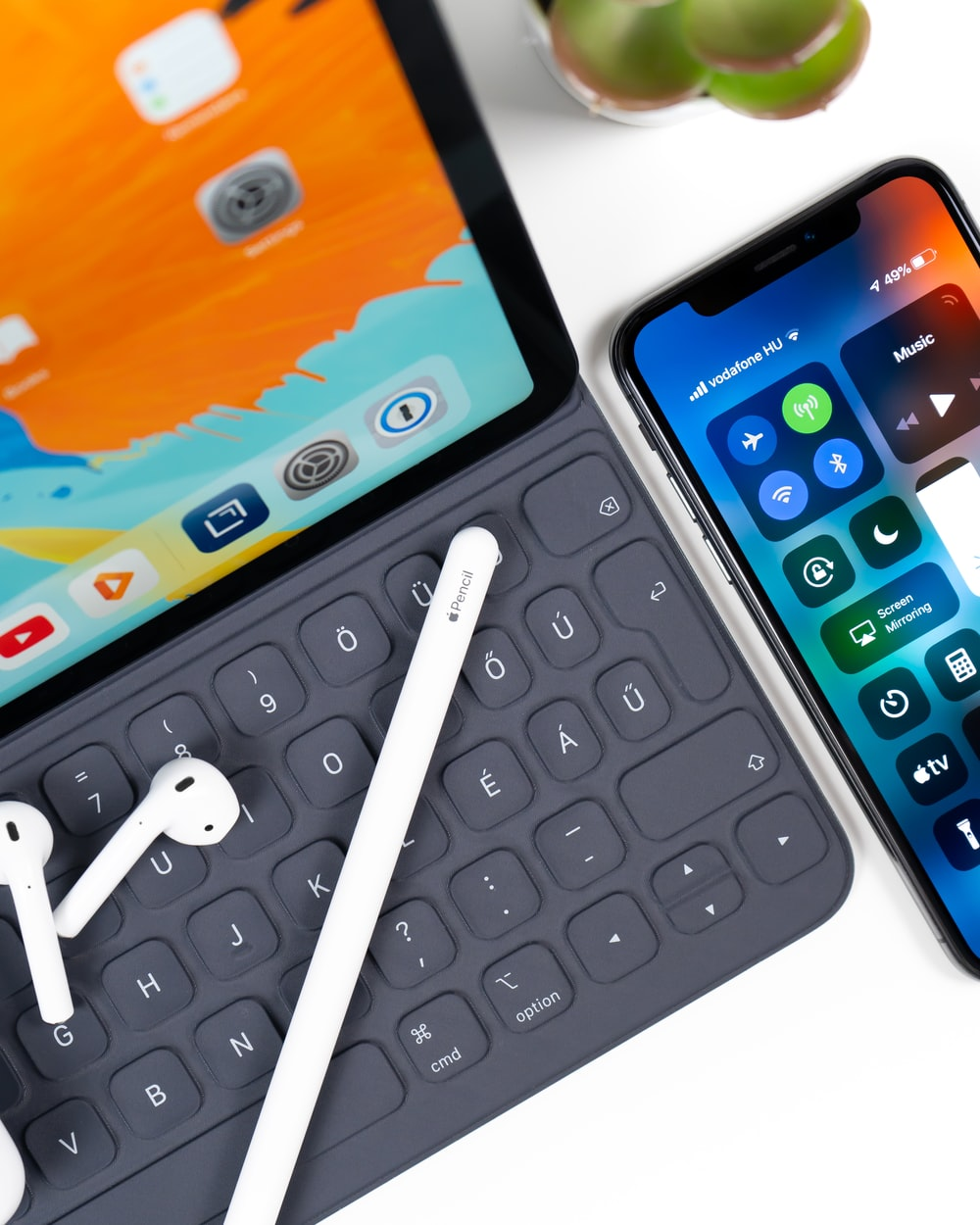 iPad with keyboard, white stylus, white AirPods; and an iphone on table