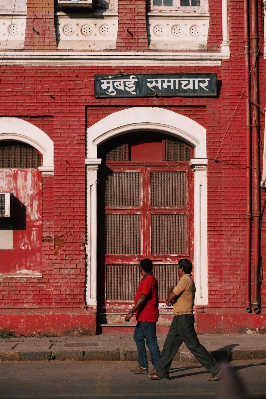 2 men walking past red building