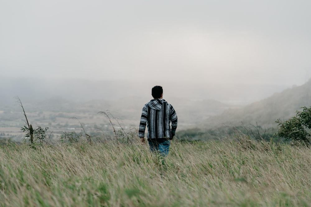man walking on grass field