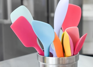 pink, blue and white plastic ladles in stainless container