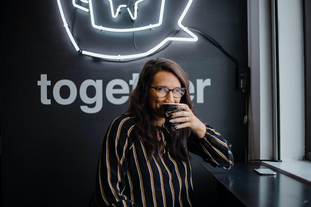 smiling woman wearing black and white stripe dress shirt zipping on mug