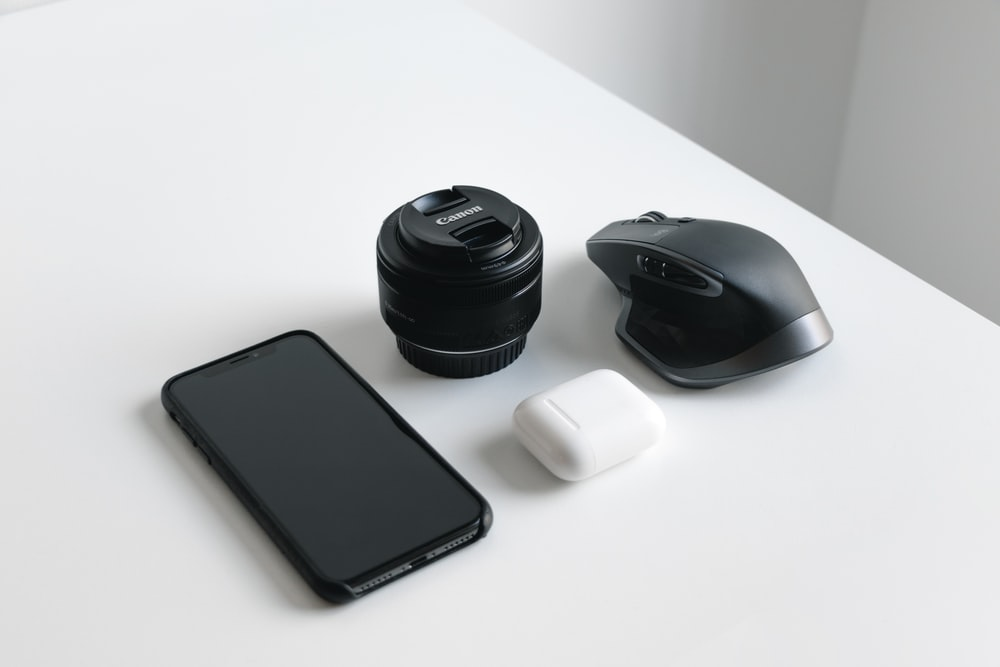 black smartphone, DSLR camera lens. and wireless computer mouse