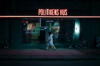 woman walking on street near Politikens Hus during nighttime