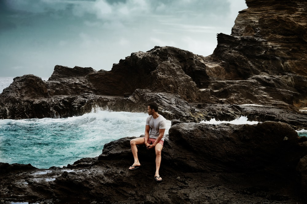 man in shirt sitting on rock formation