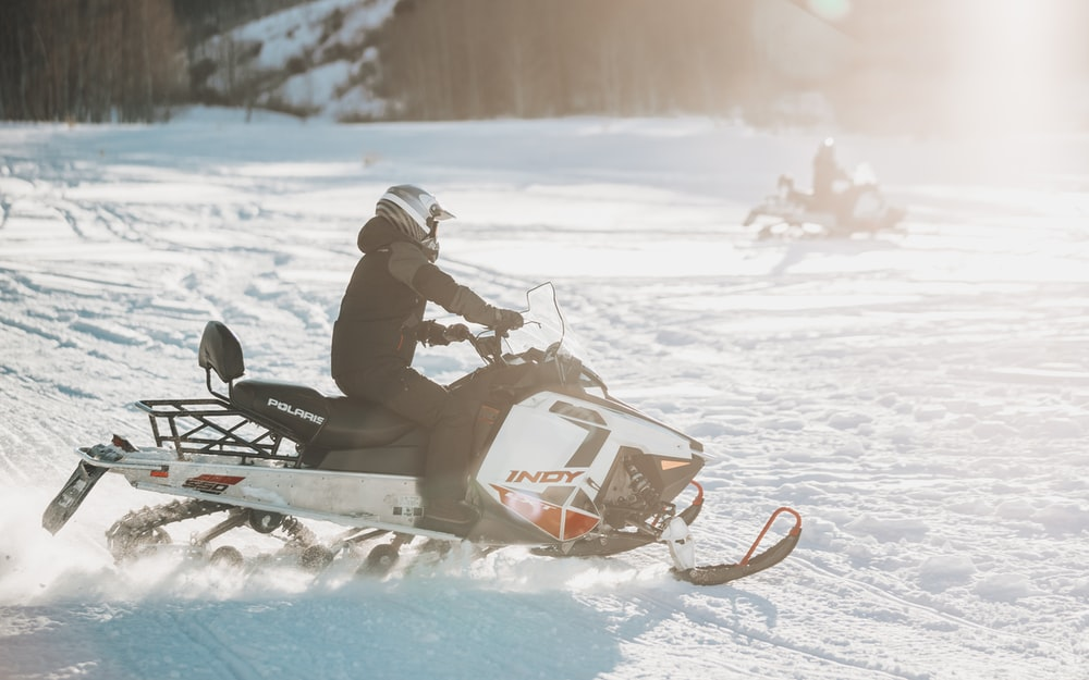 person riding snowmobile during daytime