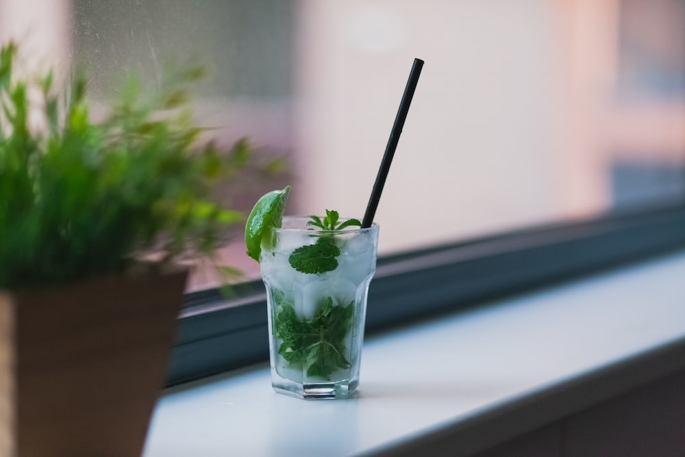 clear glass cup with liquid and green-leaf