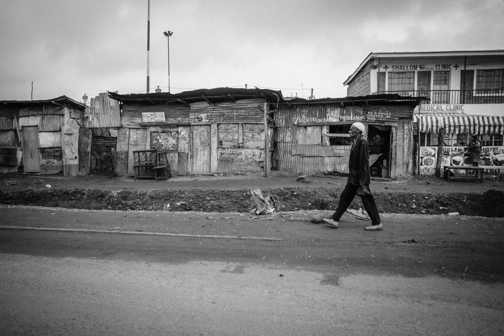 grayscale photo of man walking on road during daytime