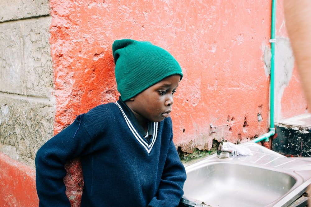 boy in green knit cap and blue sweatshirt leaning on orange painted wall beside gray stainless steel sink