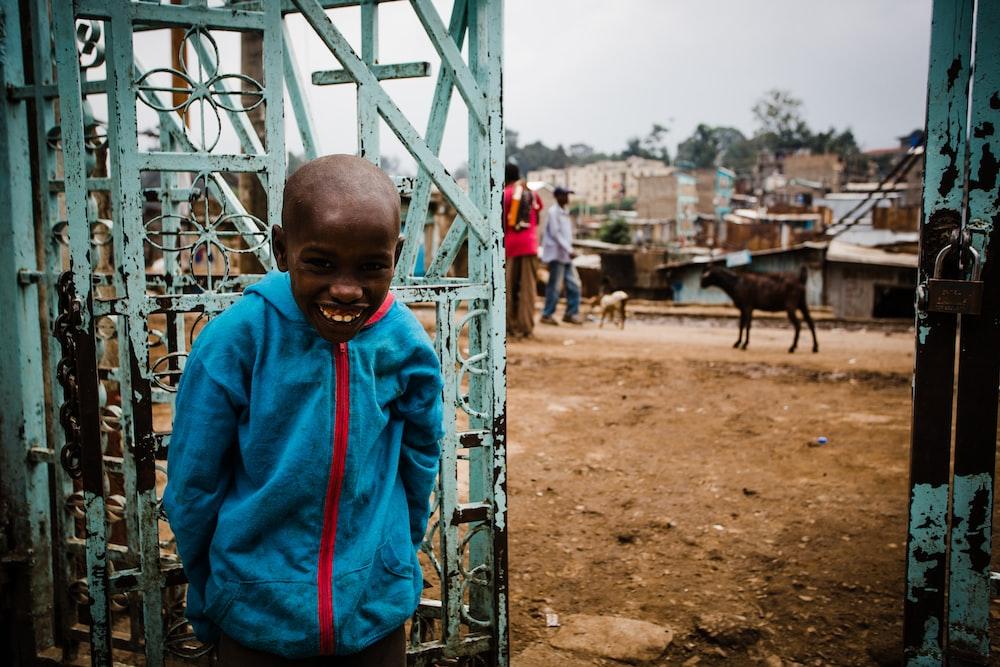 boy smiling leaning beside gate