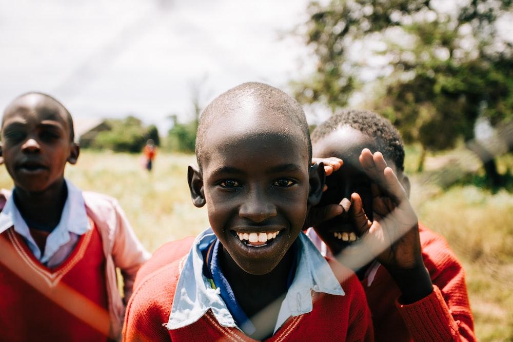 three boys smiling during daytime