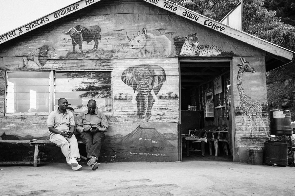 grayscale photography of two men sitting on bench
