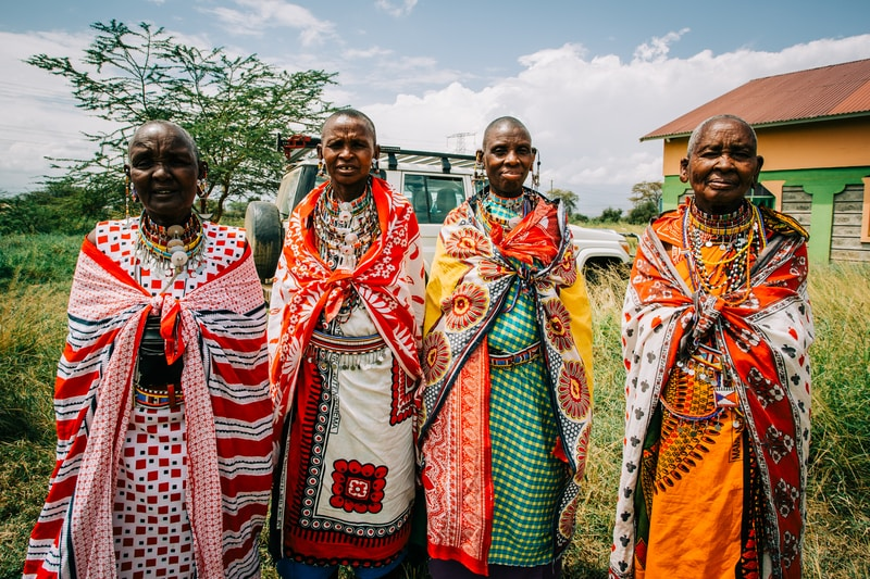 four people wearing traditional dresses