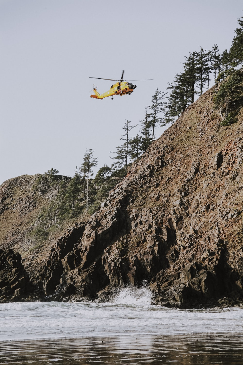 helicopter flying over body of water beside hill