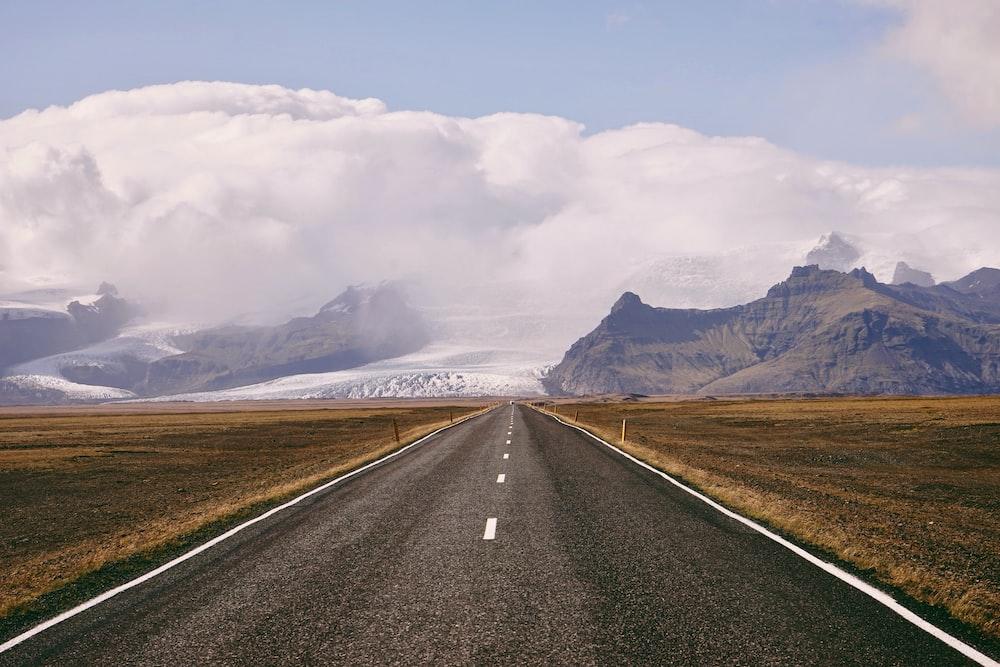 asphalt road between mountain range during daytime