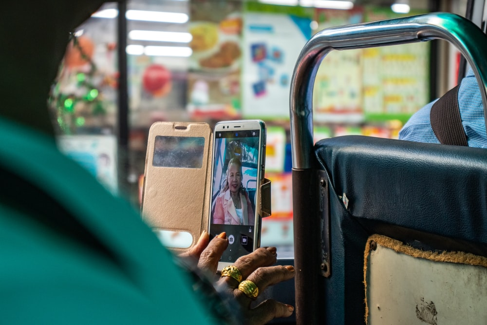 woman taking picture using smartphone inside bus