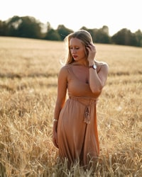 woman in brown dress in brown field