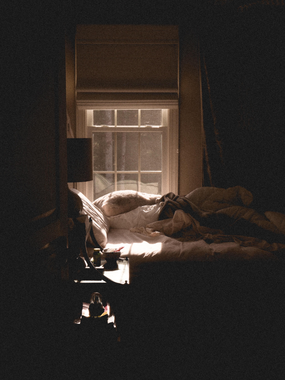 white blanket on bed beside window