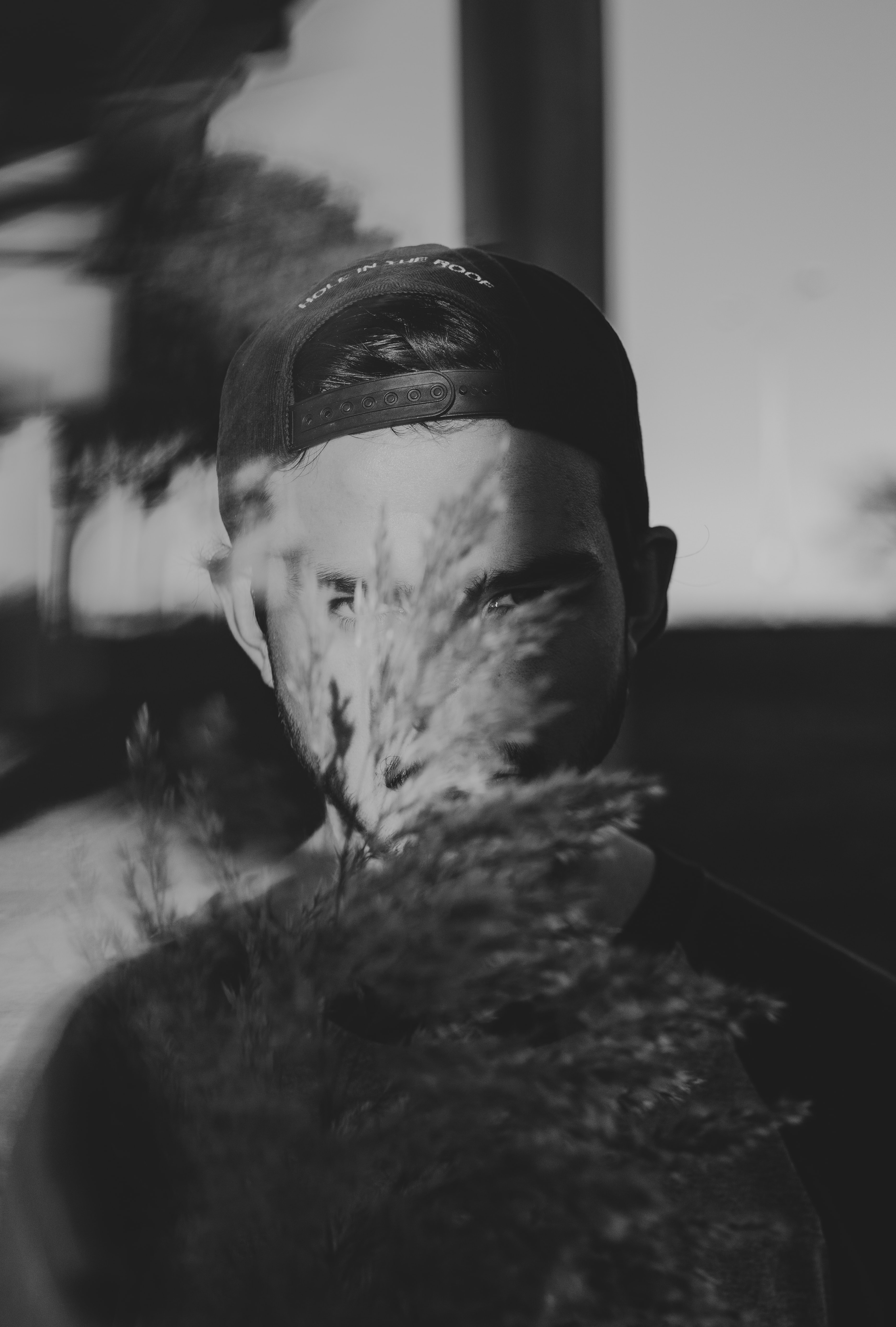 grayscale photography of man covered by plant