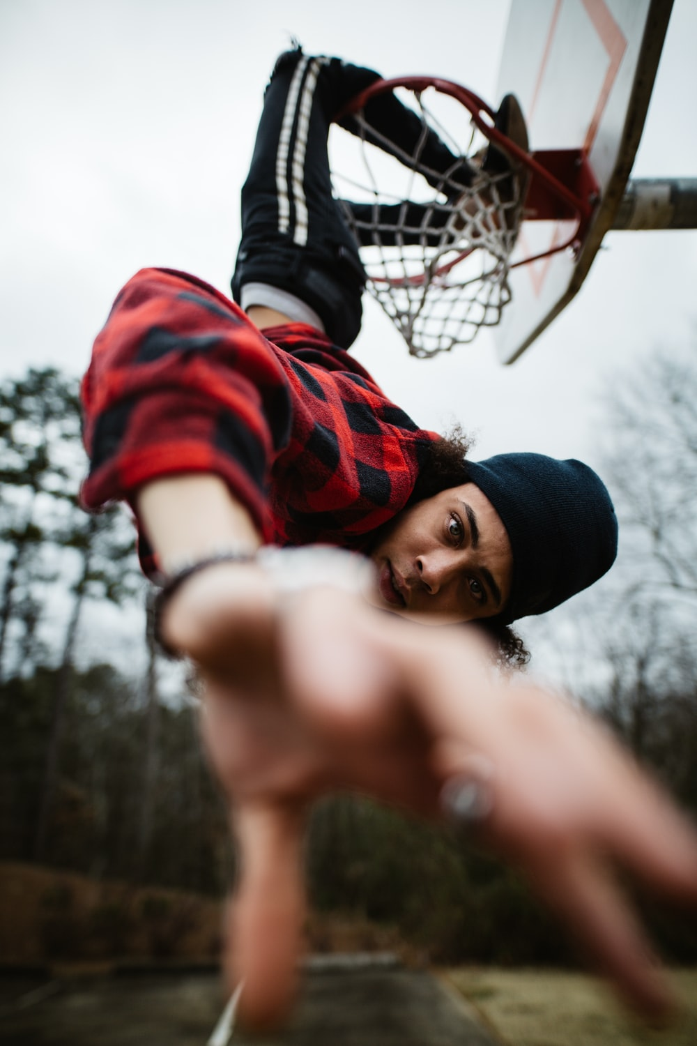 man with legs on basketball ring during daytime