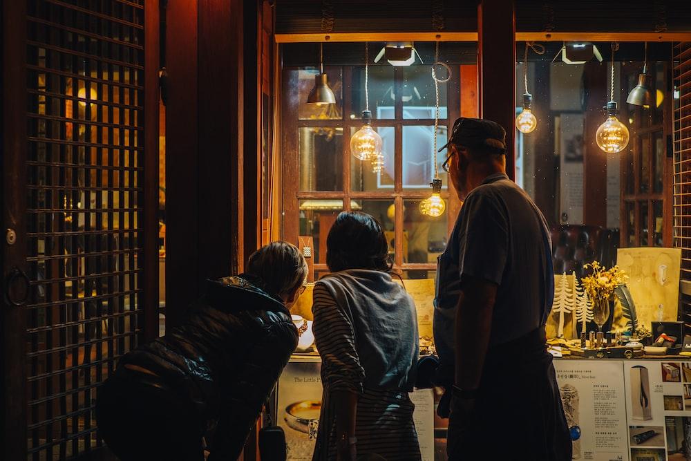 three people near glass wall