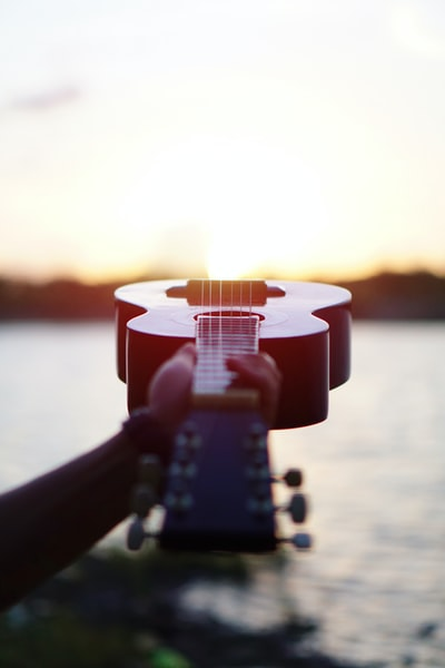 selective focus photography of acoustic guitar