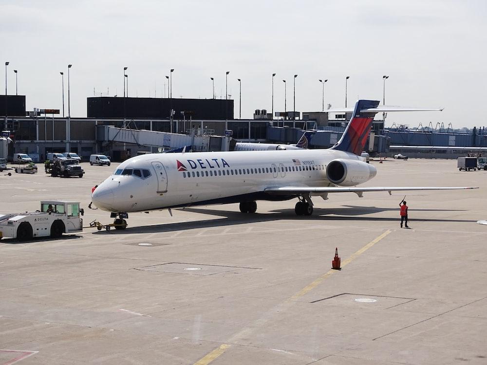 man standing beside white Delta airplane