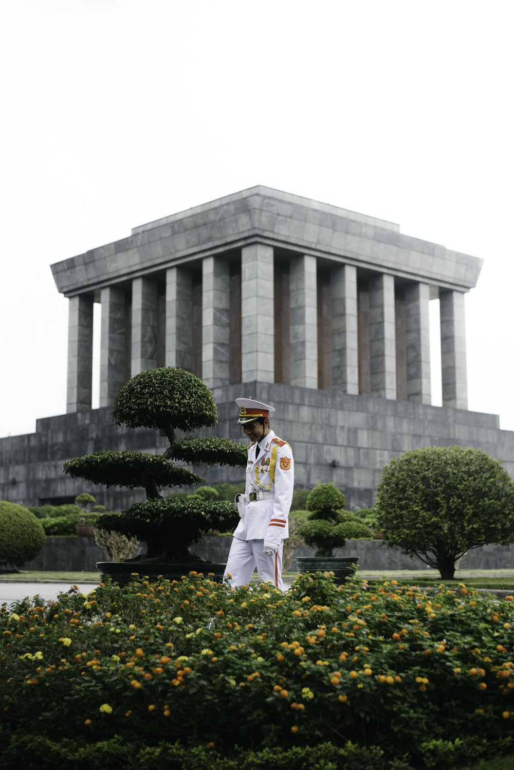 man in uniform stands beside yellow flowering plant in front of concrete museum