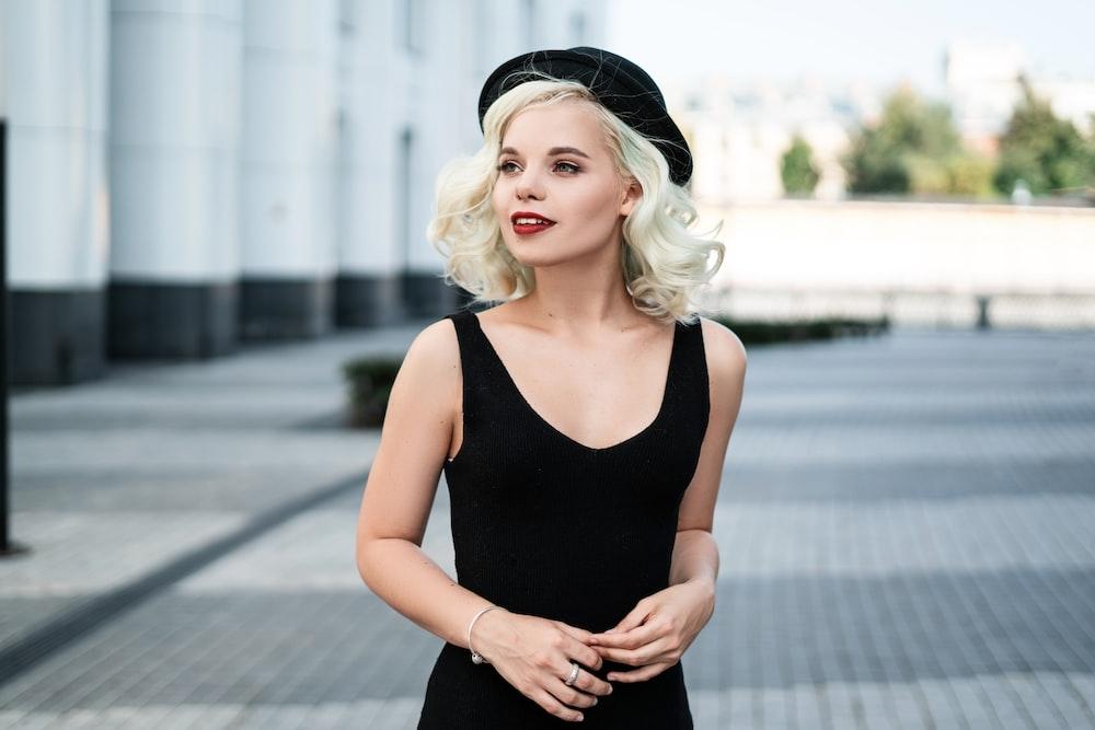 woman wearing black sleeveless top and black cap facing left