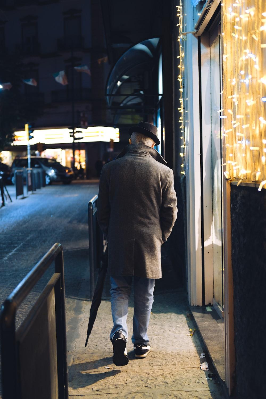 man walking beside string lights