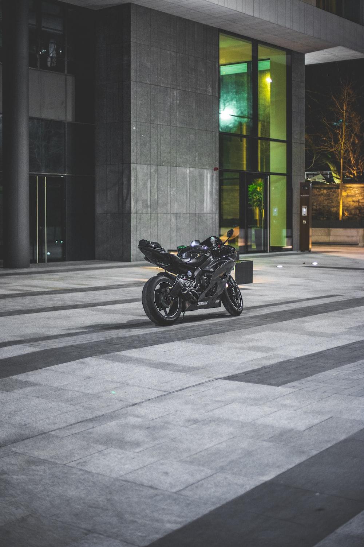 black sport bike beside building