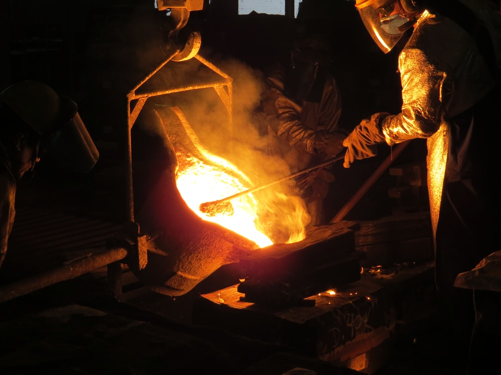 man wearing gloves and mask holding iron
