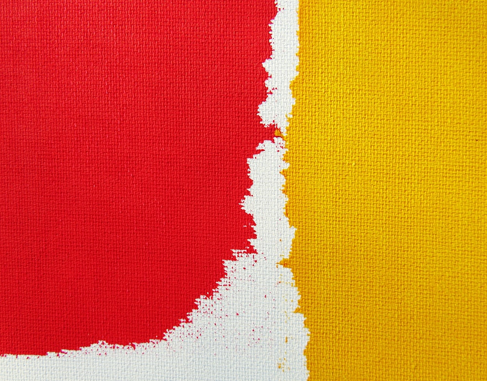 red, white, and yellow textile in closeup photo