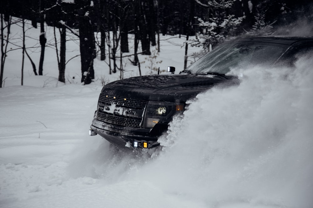 black vehicle passing on snow ground
