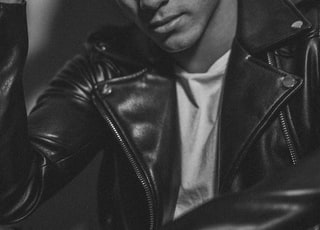 man wearing leather jacket resting head on hand