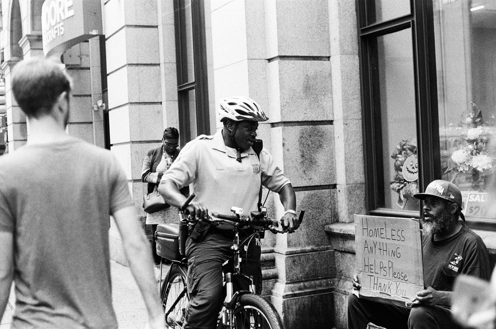 homeless sitting on the side while man riding bicycle