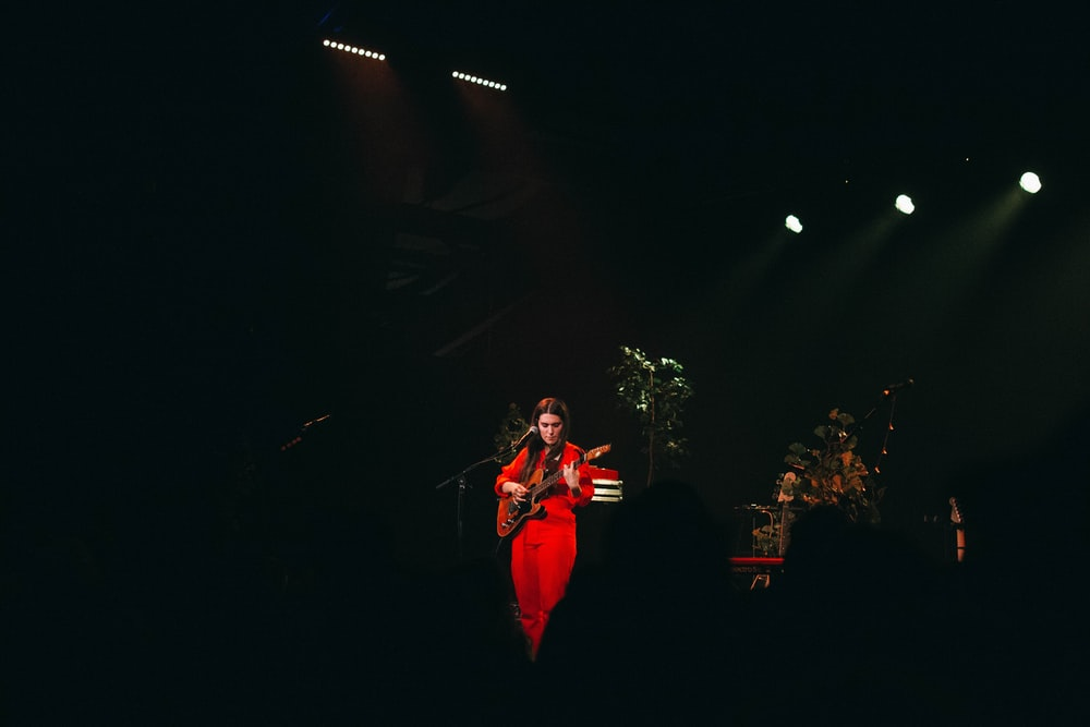 person in red clothes playing guitar