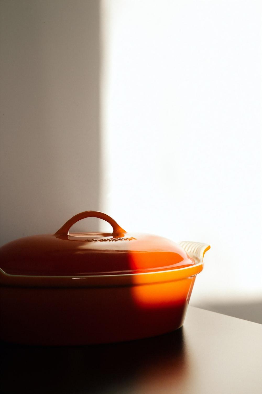 orange cooking pot on brown wooden surface