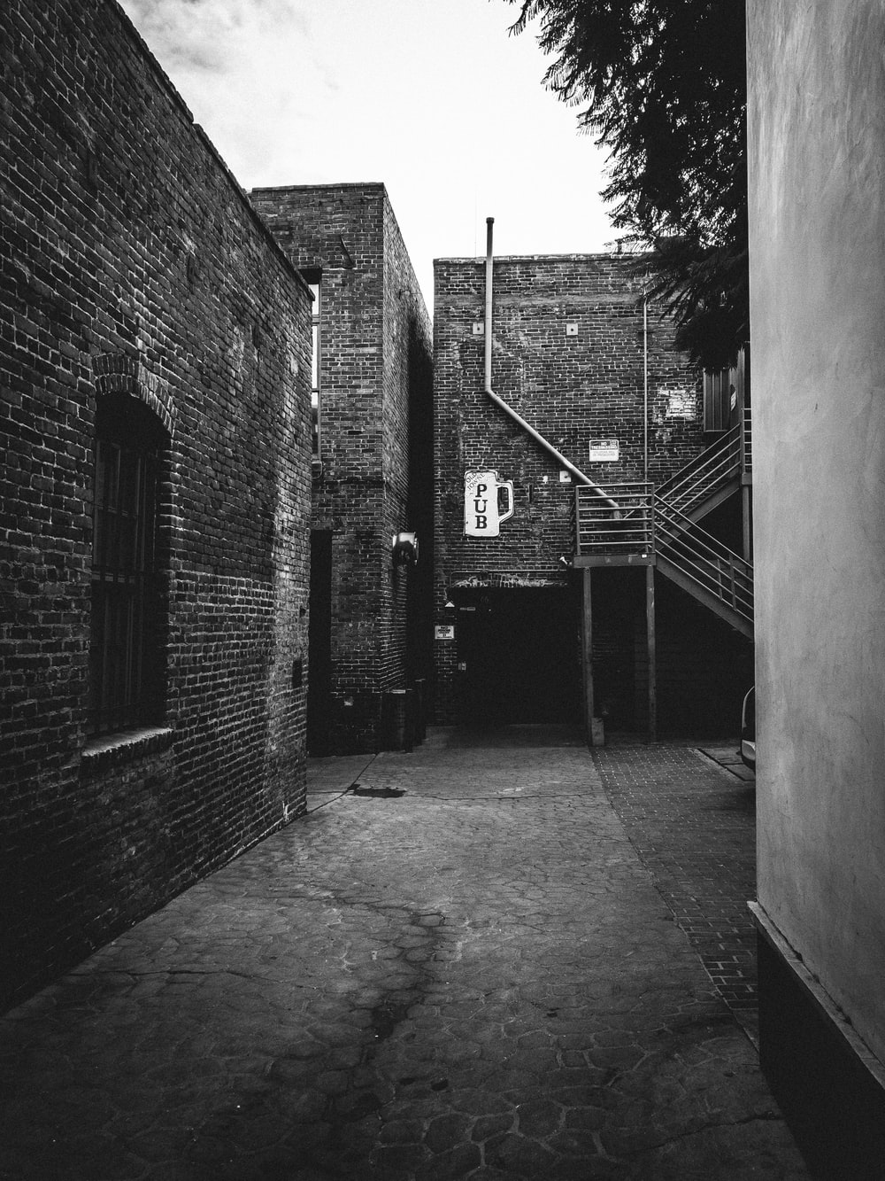 grayscale photography of alley with brick buildings
