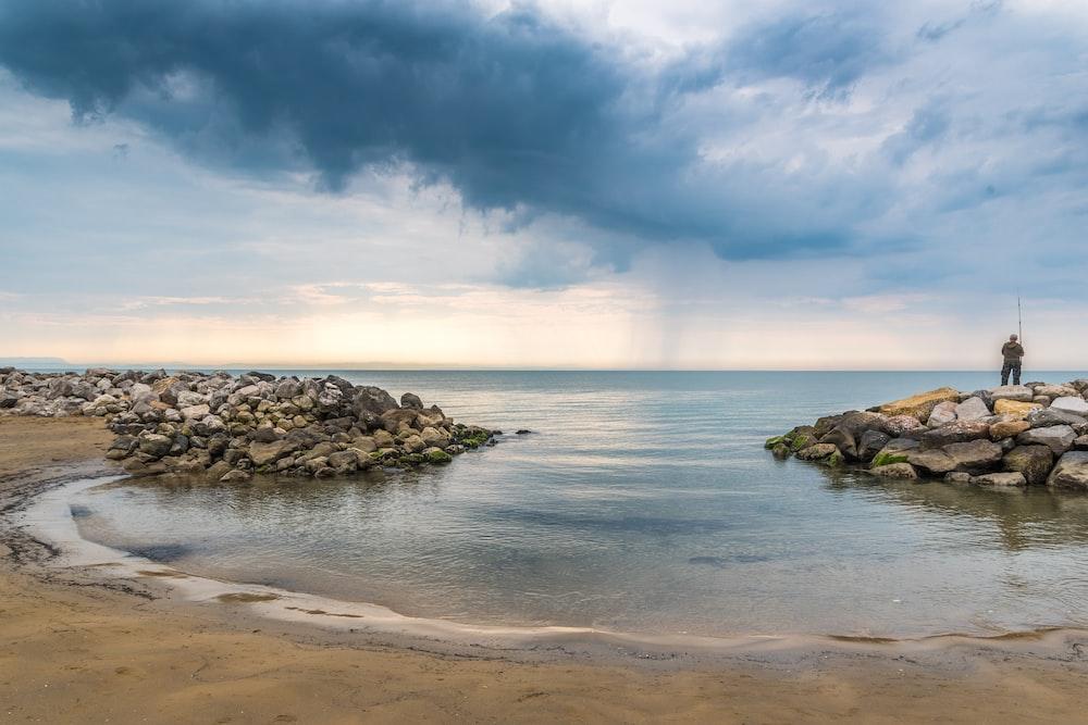 man standing on stones beside body of water