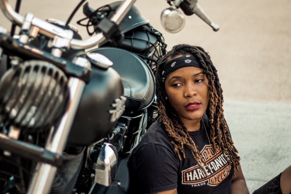 woman in black top leaning on motorcycle