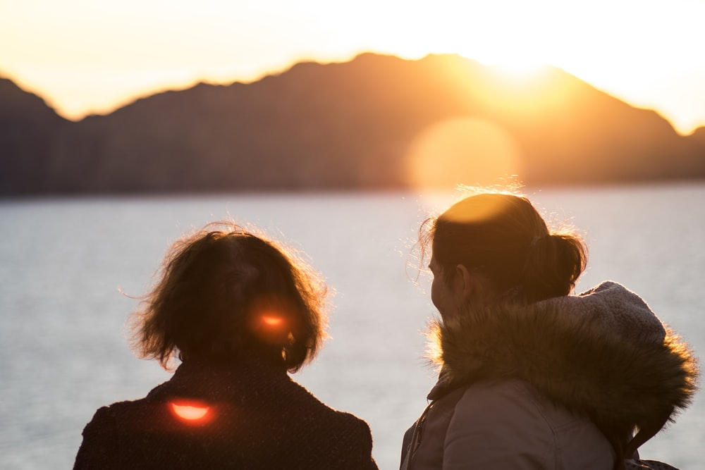 2 people standing in beach enjoying view of setting sun